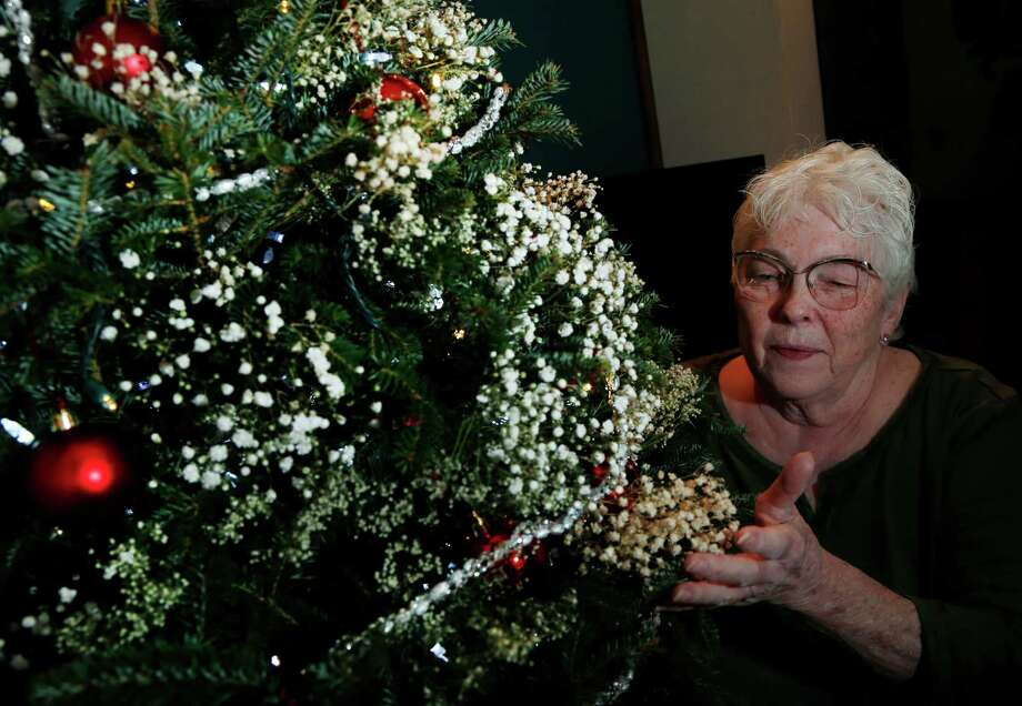 Jenny Thibault, 73, admires her tree, which she ordered online and was shipped from Mountain Star Farms in New Hampshire to her home in Beverly, Mass. A 7-foot tree costs about $50, plus $50 for shipping. Photo: Elise Amendola, STF / AP