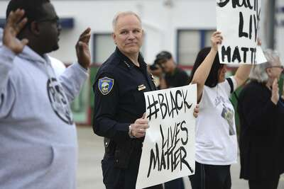 "In this photo taken Tuesday, Dec. 9, 2014, Richmond Chief of Police Chris Magnus stands with demonstrators along Macdonald Ave. to protest the Michael Brown and Eric Garner deaths during a peaceful demonstration in Richmond, Calif. The Northern California police chief noted for his community policing efforts raised a few eyebrows when he joined a peaceful protest, holding a sign with the popular Twitter hashtag of ""blacklivesmatter."" Magnus said he attended to show the department's commitment to peaceful protest and that minority lives matter. (AP Photo/Bay Area News Group, Kristopher Skinner)"