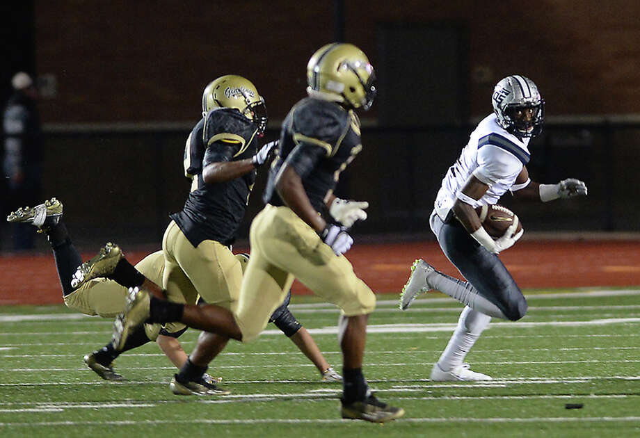 West Orange Stark's Deionte Thompson runs the ball around Giddings defenders during their play-off game Friday night in Humble.  Photo taken Friday, November 21-, 2014  Kim Brent/The Enterprise Photo: KIM BRENT / Beaumont Enterprise