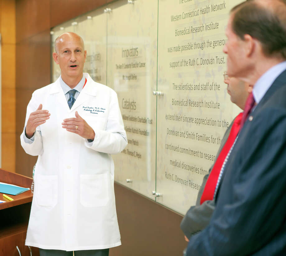 Dr. Paul Fiedler, chairman of the Western Connecticut Health Network's Department of Pathology and Laboratory medicine, speaks with Sen. Richard Blumenthal. Fiedler worked on a recently-published study showing that certain dormant viruses from the herpes family can be reactivated in people with cancer and can affect the outcome of that disease. Photo: Contributed Photo / The News-Times Contributed