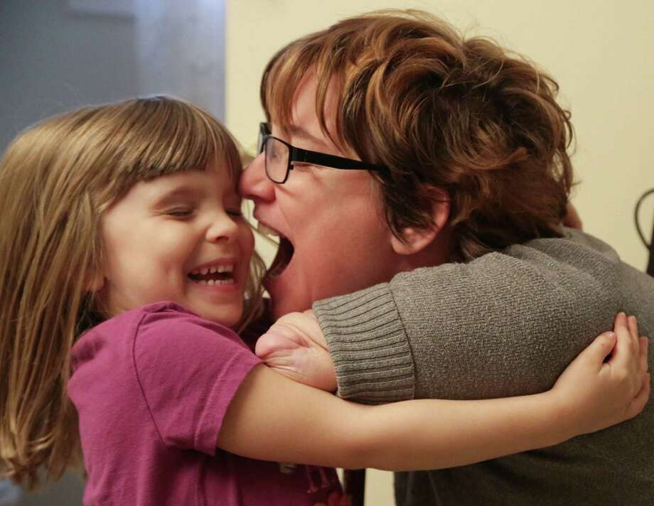 Four year-old Arielle Hayes hugs her mother Katy Hayes at their home in Kingwood. Photo: Billy Smith II, Staff / © 2014 Houston Chronicle