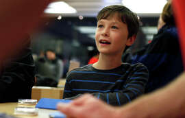 "Keaton Zon, 10, listens to Apple Store employees Devin Clary and Amy Silva, top, lead an Hour of Code class in S.F. Keaton's lessons helped him win an ""Angry Birds"" game.  Keaton Zon, 10, takes part in the Apple Store's Hour of Code initiative in S.F."