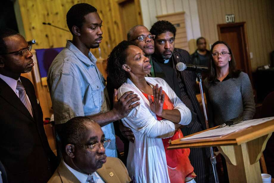 In this Monday, Dec. 1, 2014 photo, Claudia Lacy, center, cries as she thanks the people that showed up at First Baptist Church in Bladenboro, N.C., to listen to the Rev. Dr. William Barber II, president of the North Carolina State Conference of the NAACP, talk about the developments in the investigation of her son's death. Lennon Lacy, a 17-year-old, was found hanging from a swing set in the middle of a trailer park in late August. Surrounding Claudia Lacy are attorney Alan Rogers, left, Wilson Lacy, sitting, Lennon' brother Pierre Lacy, Rev. Gregory D. Taylor, Rev. William Barber II and attorney Heather Rattelade. (AP Photo/The Fayetteville Observer, Raul R. Rubiera) MANDATORY CREDIT Photo: Raul R. Rubiera, MBO / The Fayetteville Observer