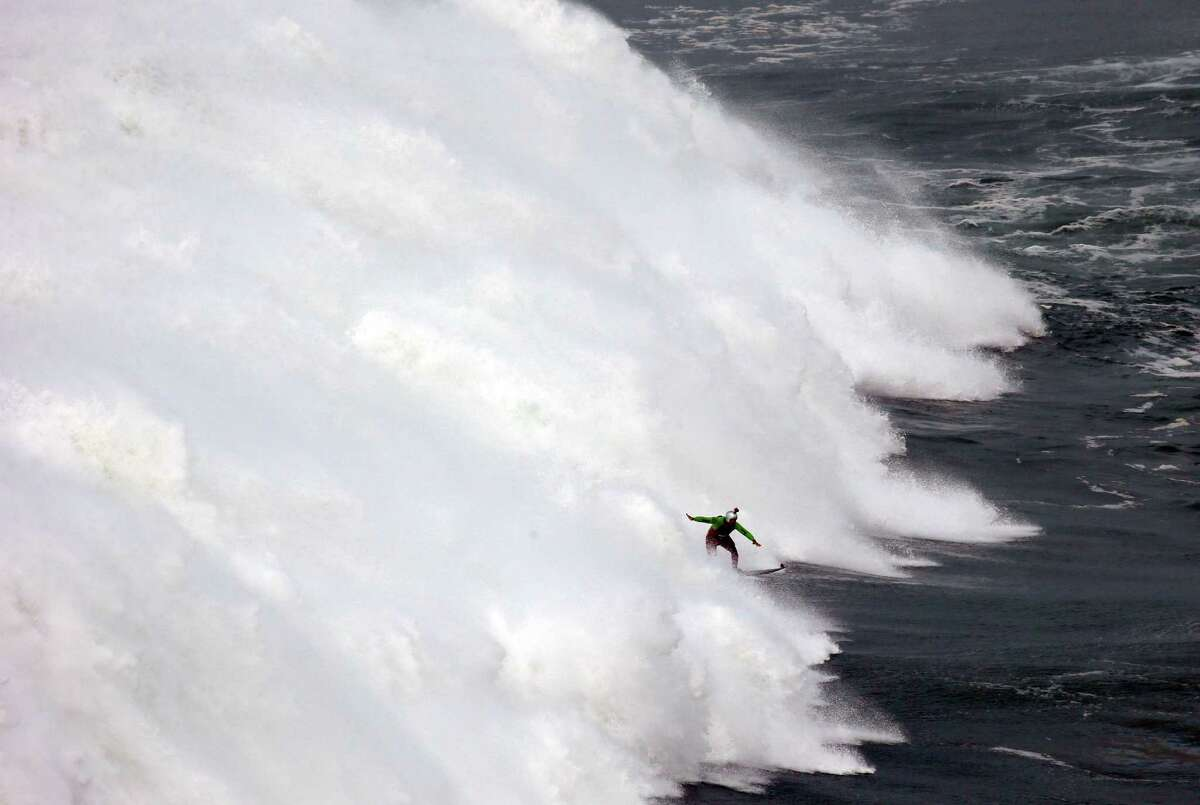 US surfer Garrett McNamara rides a big wave during a tow-in surfing session at the Praia do Norte or North beach, in Nazare, Portugal, Friday, Dec. 12, 2014. McNamara set a world record for the largest wave surfed when he rode a 23.7 metre wave (78-foot) in Nazare in 2011.