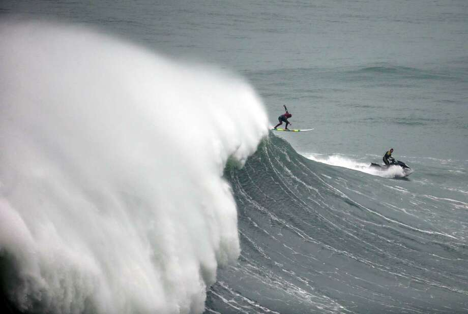 A surfer drops a big wave during a surfing session at the Praia do Norte or North beach, in Nazare, Portugal, Friday, Dec. 12, 2014.  Photo: Francisco Seco, Associated Press / AP
