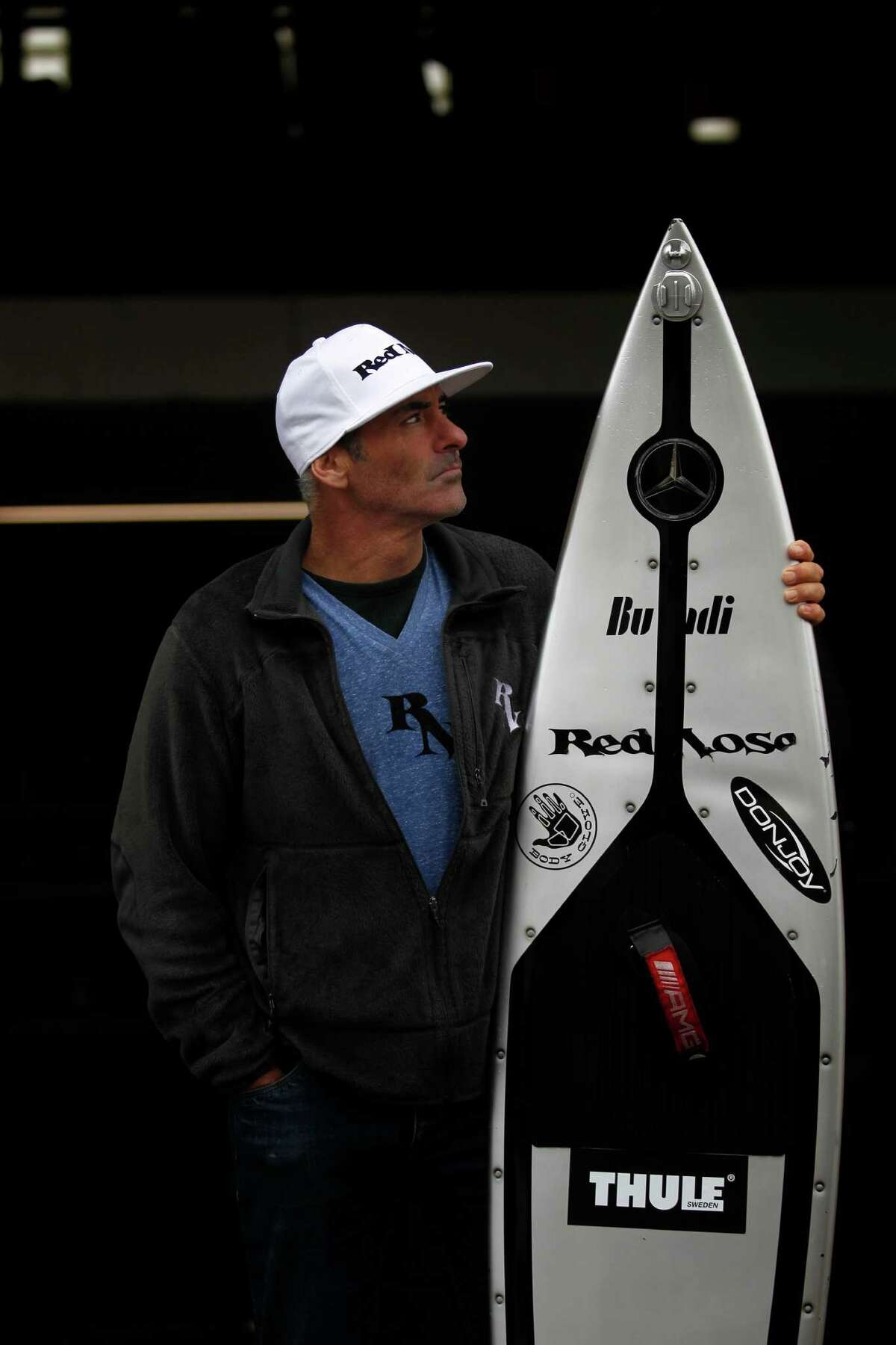US surfer Garrett McNamara looks at his surfboard while he is interviewed by a Portuguese TV channel after a tow-in surfing session at the Praia do Norte or North beach, in Nazare, Portugal, Friday, Dec. 12, 2014. McNamara set a world record for the largest wave surfed when he rode a 23.7 metre wave (78-foot) in Nazare in 2011.