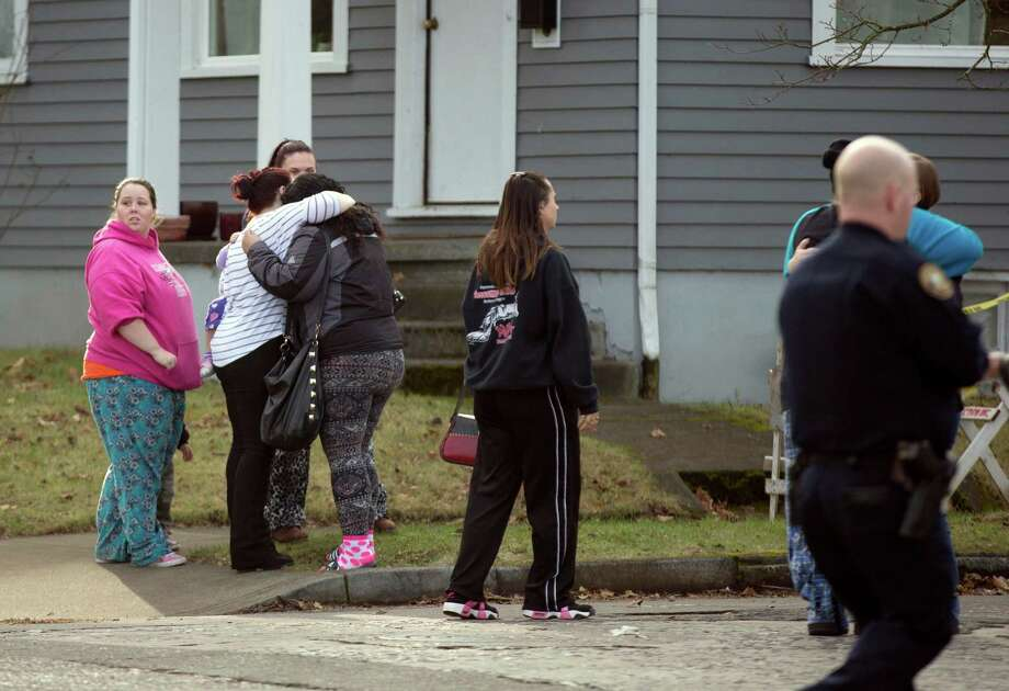 Family members greet their children who were escorted out of Rosemary Anderson High School in North Portland after a shooting on Dec. 12, 2014. A shooter wounded two boys and a girl outside a U.S. high school Friday in what is believed to be a gang-related attack, police said. (AP Photo/The Oregonian, Kristyna Wentz-Graff) Photo: Kristyna Wentz-Graff, MBI / The Oregonian