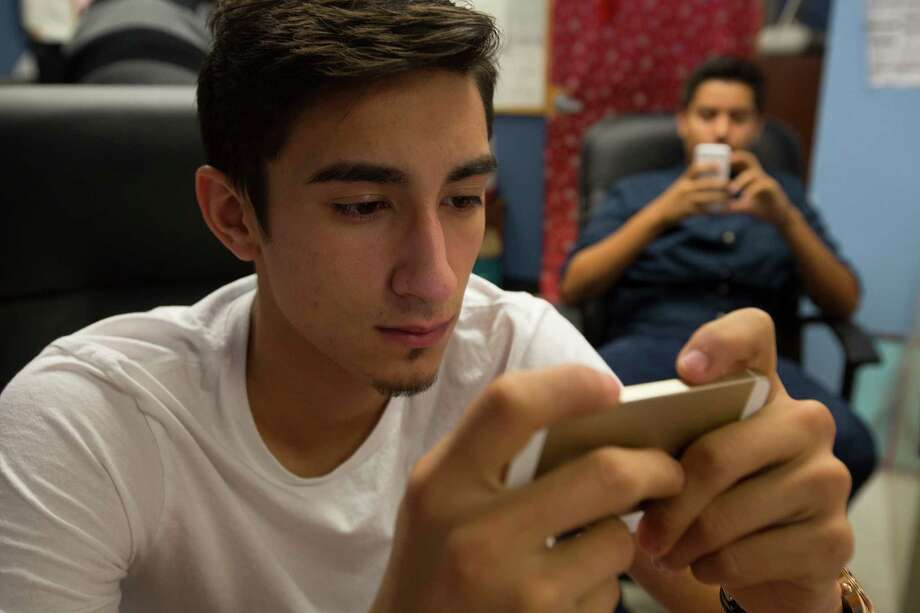 Eastwood Academy High School seniors Jose Calles, left, and Ricardo Garcia, both 17, gave up on the national technology timeout challenge and quickly turned to their phones for games. Photo: Johnny Hanson, Staff / © 2014  Houston Chronicle