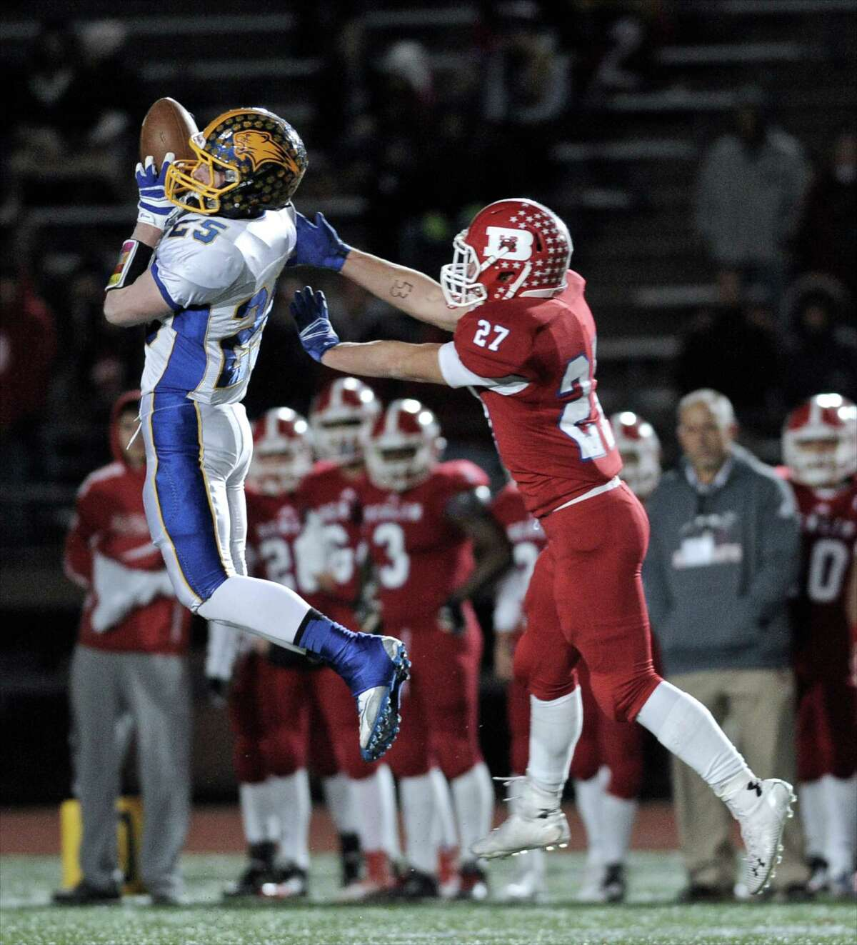 Brookfield's Gabe Pompette (25) intercepts a pass intended for Berlin's Anthony Sisti (27), Pompette took the ball in for a touchdown, during the Connecticut state high school Class M-Large football championship game between Berlin and Brookfield high schools played at Veterans Memorial Stadium, in New Britain, Conn, on Friday night, December 12, 2014. Brookfield won the state championship 14-0.