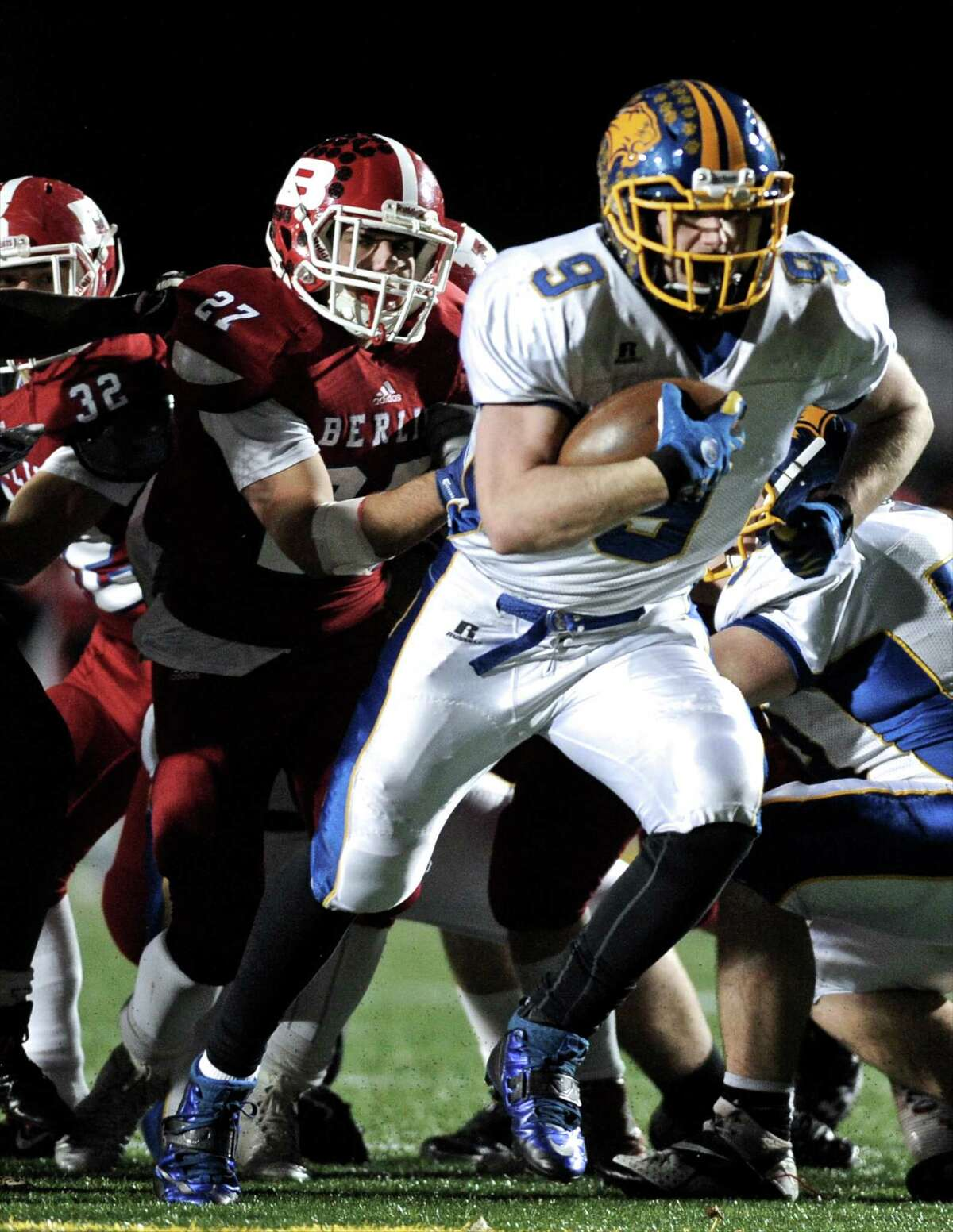 Brookfield's Bobby Drysdale (9) breaks away from Berlin's Anthony Sisti (27) to score a touchdown during the Connecticut state high school Class M-Large football championship game between Berlin and Brookfield high schools played at Veterans Memorial Stadium, in New Britain, Conn, on Friday night, December 12, 2014. Brookfield won the state championship 14-0.
