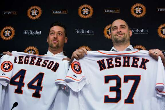 Luke Gregerson, left, and Pat Neshek, right, show their new Houston Astros jersey during a press conference at the Minute Maid Park. Astros general manager Jeff Luhnow announced the addition, Friday, Dec. 12, 2014, in Houston.