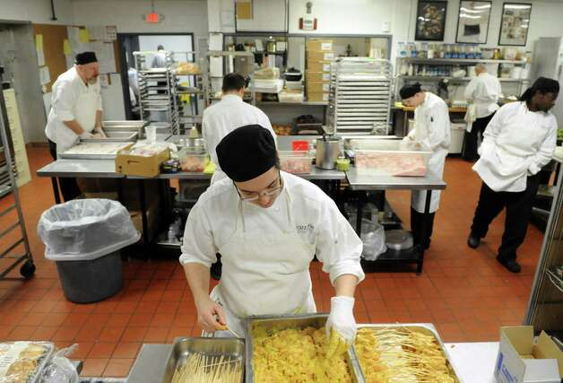 Cook Kelmy Tejada, center, prepares a tray of chicken satay as the kitchen team gets food ready for a holiday party Friday, Dec. 12, 2014, at the Mazzone Hospitality catering kitchen in Clifton Park , N.Y.  (Michael P. Farrell/Times Union) Photo: Michael P. Farrell / 00029833A