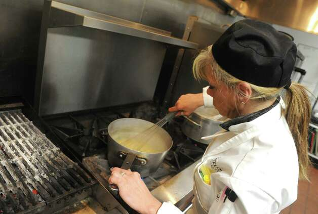 Event Chef Wendy Milavec whisks a sauce as the kitchen team gets food ready for a holiday party Friday, Dec. 12, 2014, at the Mazzone Hospitality catering kitchen in Clifton Park , N.Y.  (Michael P. Farrell/Times Union) Photo: Michael P. Farrell / 00029833A