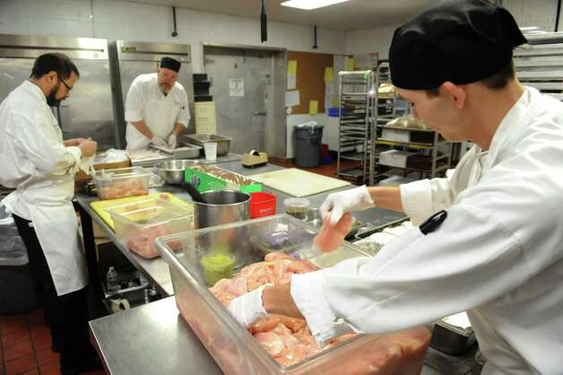 Prep cook Christopher Rock, right, flours chicken breast as the kitchen team gets food ready for a holiday party Friday, Dec. 12, 2014, at the Mazzone Hospitality catering kitchen in Clifton Park , N.Y.  (Michael P. Farrell/Times Union) Photo: Michael P. Farrell / 00029833A