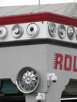The tire and auto repair shop at 16th and Shotwell streets dates back to 2860 and has what is called a Mediterranean Eclectic design. But the eye-catching features are more recent: hub caps creating a cornice line and friendly graffiti on the garage doors.