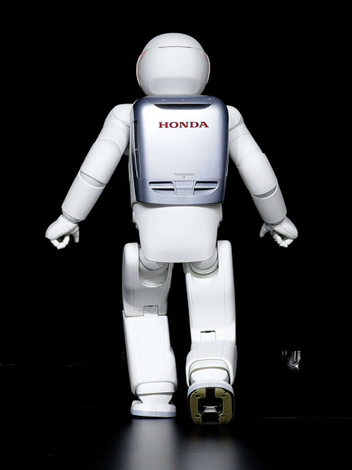 Almost human: Honda's robot, Asimo, can run forward and backward and hop on one foot. The Asimo Robot walks behind a curtain at the New York International Auto Show in New York, Thursday, April 17, 2014. (AP Photo/Seth Wenig) Photo: Seth Wenig / ASSOCIATED PRESS / ONLINE_CHECK