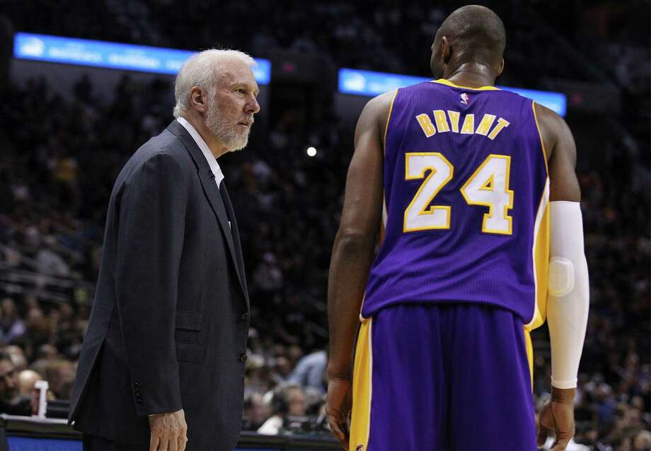 Spurs' head coach Gregg Popovich (left) briefly chats with Los Angeles Lakers' Kobe Bryant (24) during a timeout at the AT&T Center on Friday, Dec. 12, 2014. (Kin Man Hui/San Antonio Express-News) Photo: Kin Man Hui, Staff / San Antonio Express-News / ©2014 San Antonio Express-News