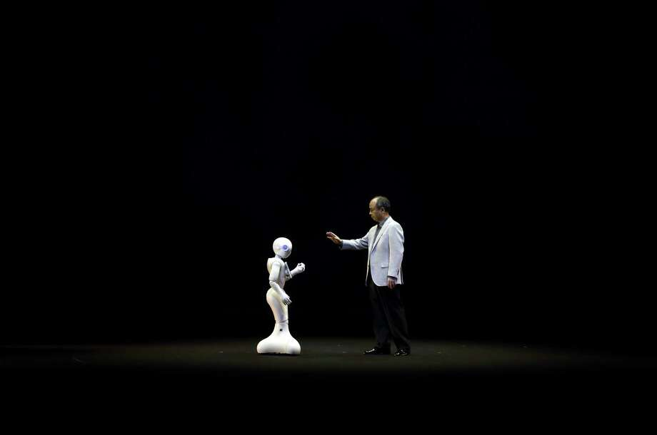 Masayoshi Son, chairman and CEO of SoftBank Corp., interacts with a human-like robot called Pepper during a news conference this year. Pepper is designed to talk with humans, using software that can recognize emotions in voices and facial  expressions. Photo: Tomohiro Ohsumi / © 2014 Bloomberg Finance LP