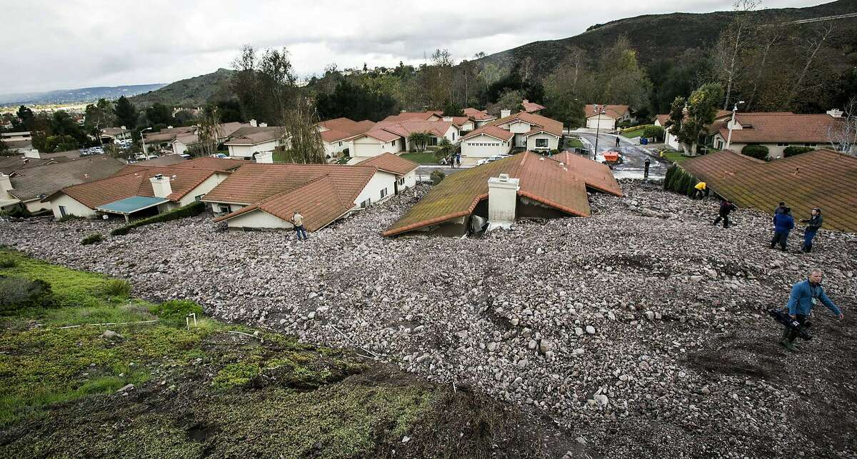 Debris and rocks fill the backyards of homes along San Como Lane in Camarillo Springs, Calif., after a storm on Friday, Dec. 12, 2014. Mountainsides stripped bare by a wildfire last year belched a damaging debris flow into the Southern California community during a downpour from a major Pacific storm early Friday. (AP Photo/Ringo H.W. Chiu)