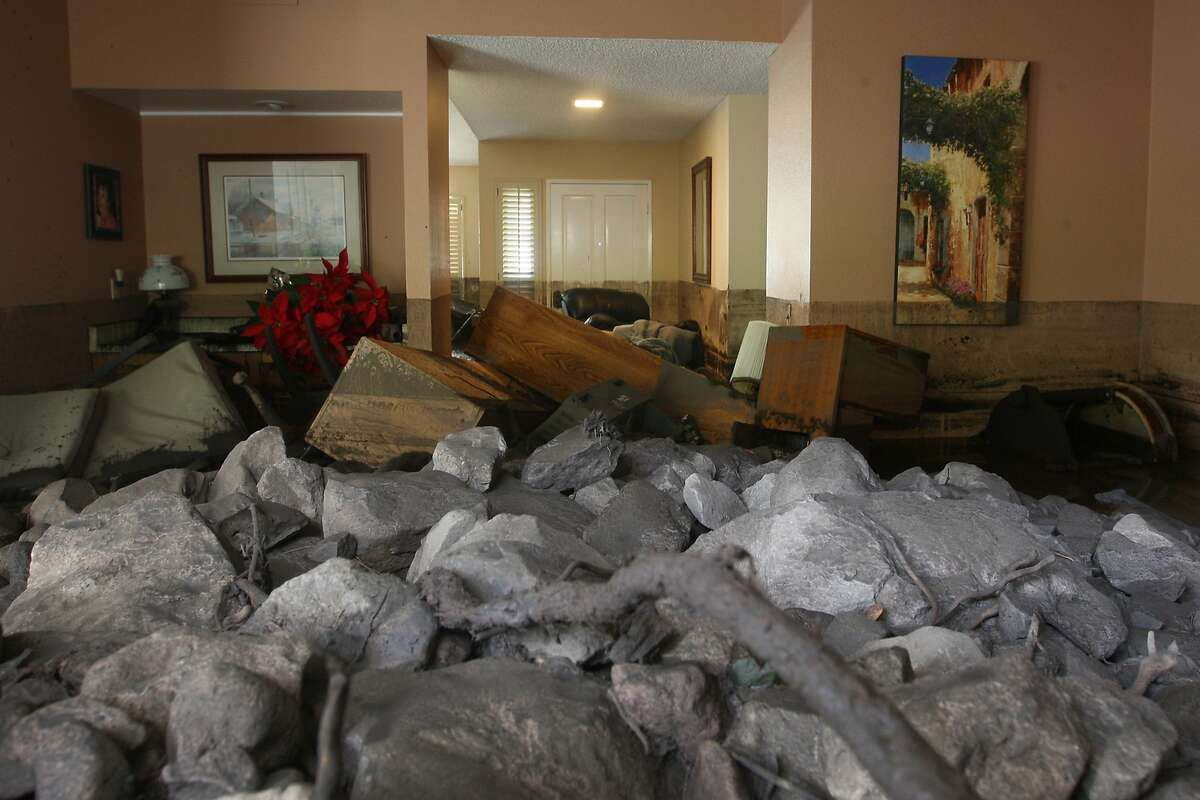 CAMARILLO, CA - DECEMBER 12: A home is filled with rocks and mud after debris flows smashed into homes as a powerful storm that has been lashing northern California moves southward on December 12, 2014 in Camarillo Springs neighborhood of Camarilla, California. About two dozen homes were severely damage in a heavy pre-dawn downpour. Although water from the storm lowers the risk of wildfires and offers some short-term relief from the record drought conditions that are menacing the state, weather experts say it amounts to only a very small step toward ending the drought. (Photo by David McNew/Getty Images) *** BESTPIX ***