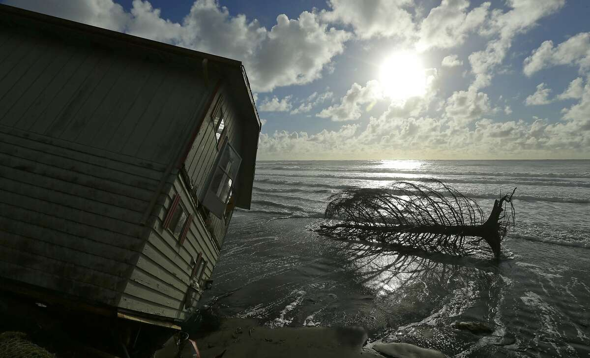 A two-story house that toppled over the eroding ocean shoreline of North Cove, Wash. sits near an uprooted tree, Friday, Dec. 12, 2014, as the tide rises. Stormy weather blew out of Washington state on Friday, but left several houses in the area damaged in its wake. (AP Photo/Ted S. Warren)