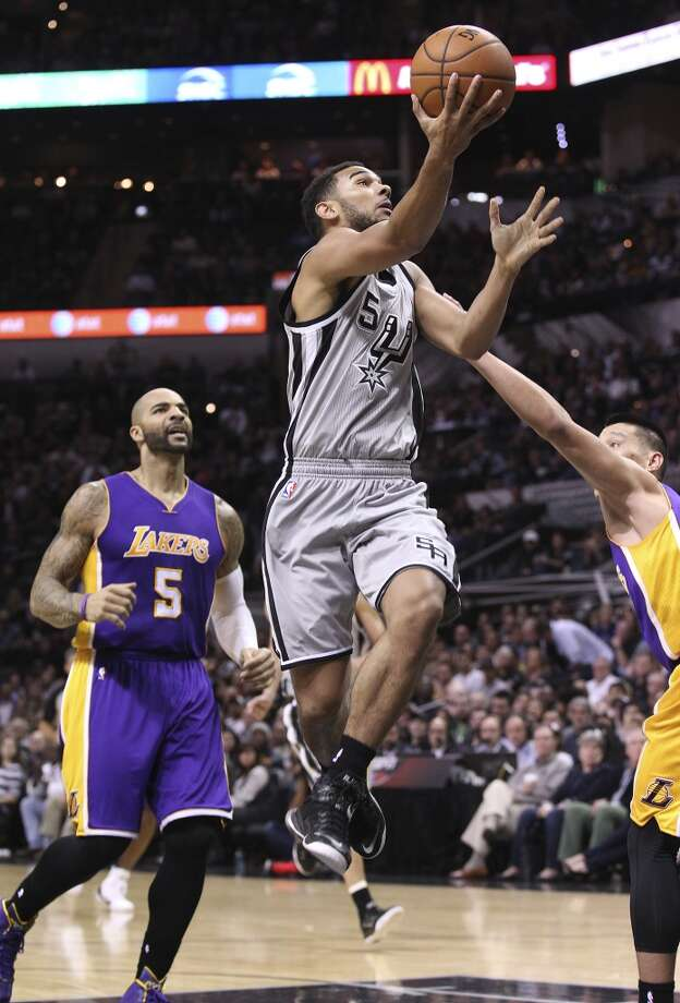 Spurs' Cory Joseph (05) drives the lane for a basket against Los Angeles Lakers' Carlos Boozer (05) and Jeremy Lin (17) at the AT&T Center on Friday, Dec. 12, 2014. (Kin Man Hui/San Antonio Express-News) Photo: San Antonio Express-News