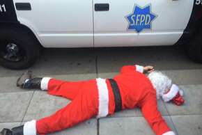 A SantaCon patron lies in front of an SFPD car after being pushed out of Union Square in prep for protests.