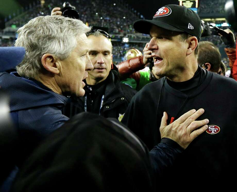 Coach Jim Harbaugh (right) congratulates Pete Carroll after his Seahawks beat the 49ers in the NFC Championship Game. Photo: Ted S. Warren / Associated Press / AP