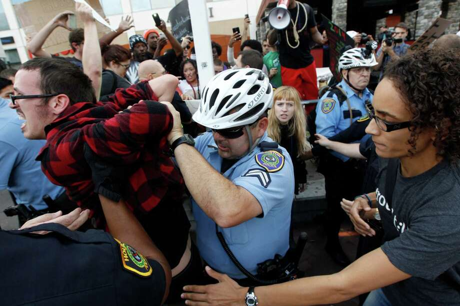 A protester is arrested during a demonstration outside the Galleria 
