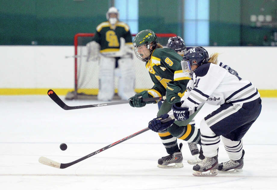 At left, Charlotte Gilliland (#9) of Greenwich Academy goes for the puck along with Millbrook's Olivia Ferraro (#21) during the girls high school ice hockey game between Greenwich Academy and the Millbrook School at Chelsea Piers in Stamford, Conn., Saturday, Dec. 13, 2014. Photo: Bob Luckey / Greenwich Time