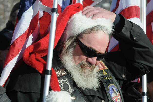 Patriot Guard Tim Bliss of Scotia takes off his Santa hat during the Pledge of Allegiance during a ceremony for National Wreaths Across America Day at the Gerald Solomon National Cemetery on Saturday Dec. 13, 2014 in Schuylerville , N.Y.  (Michael P. Farrell/Times Union) Photo: Michael P. Farrell / 00029839A