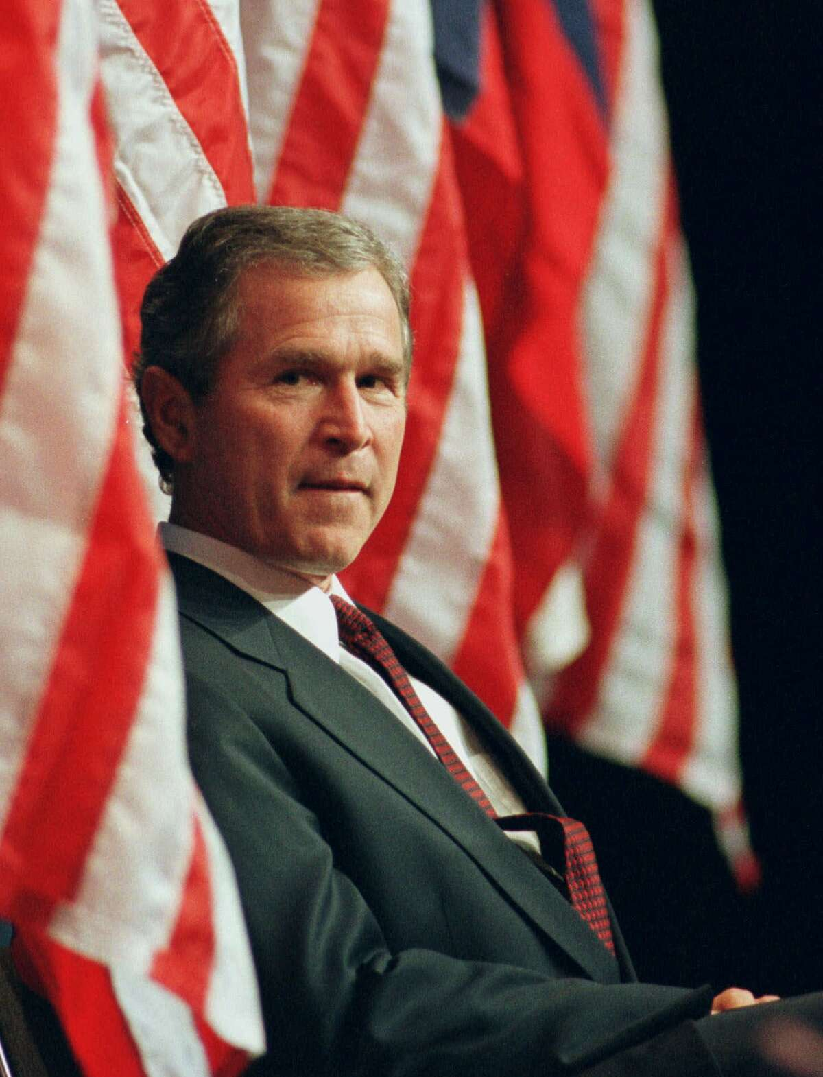 Texas Gov. George W. Bush is flanked by U.S. flags on stage at the Convention Center in Austin, Texas, on Sunday March 7, 1999. (AP Photo Harry Cabluck)