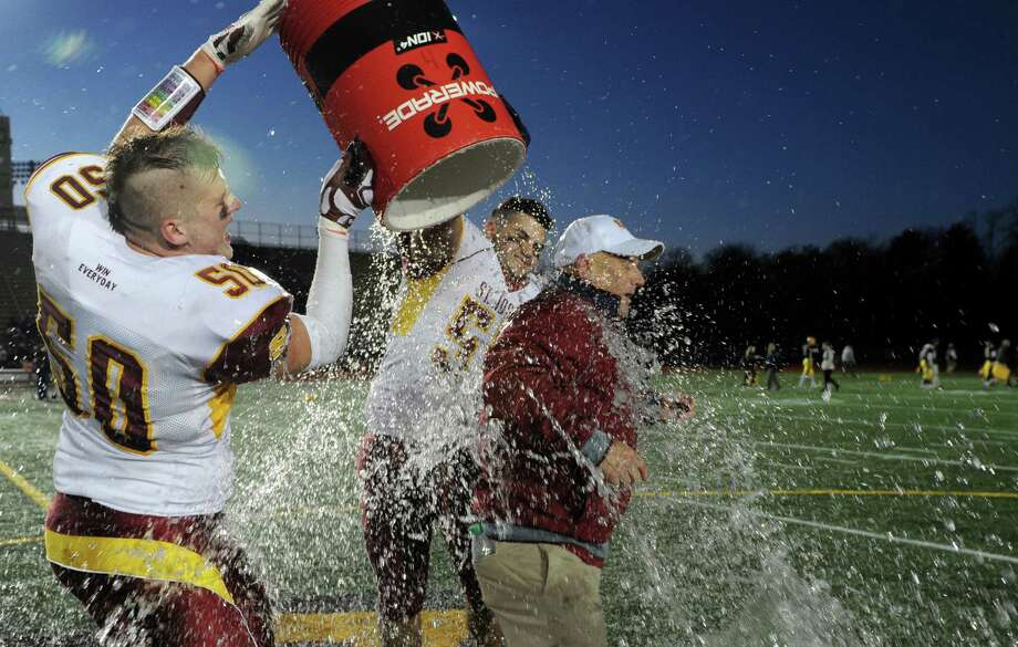 St. Joseph players Konrad Piszczatowski, left, and Troy Vazzano dump a bucket of ice water on Head Coach Joe DellaVecchia Saturday, Dec. 13, 2014, following the football team's Class M-Small state championship 37-7 win over Ledyard at Veterans Memorial Stadium in New Britain, Conn. Photo: Autumn Driscoll / Connecticut Post