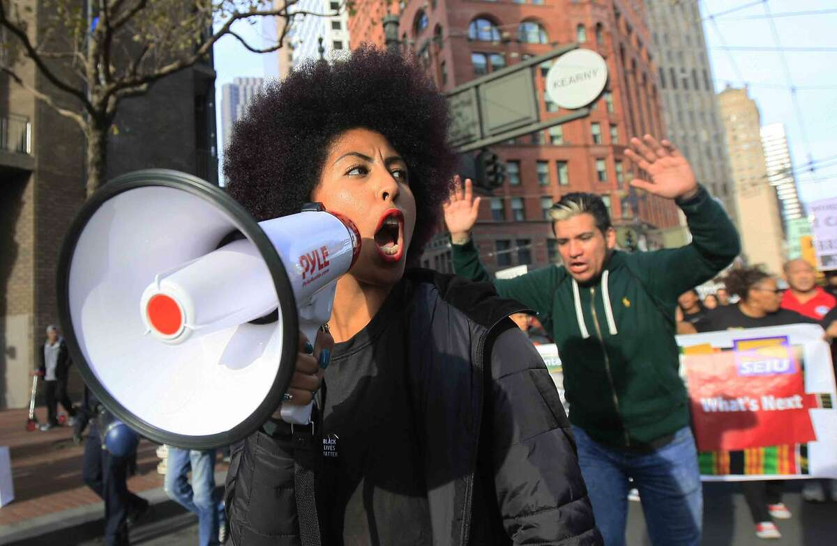 Thea Matthews chants through a megaphone in San Francisco, Calif. Saturday, December 13, 2014 during a protest against the police killings of Eric Garner in Staten Island, New York and Michael Brown in Ferguson, Missouri.