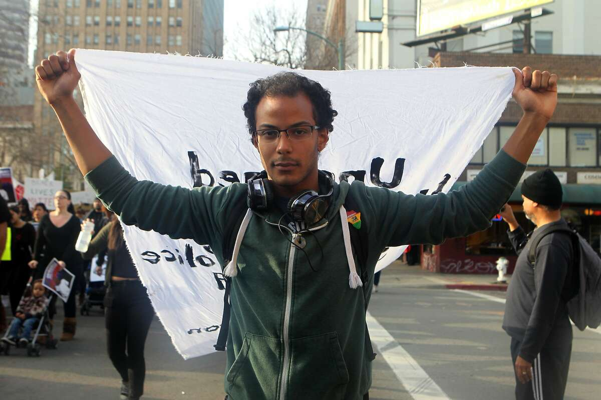 Daniel Hunter holds a banner up while walking down 14th st. during the
