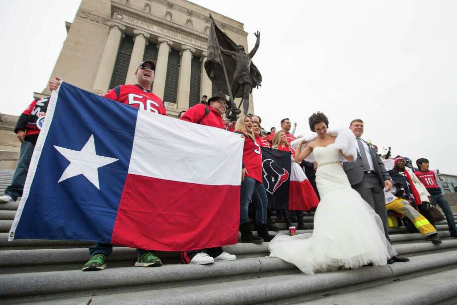 The Texans won't be alone Sunday when they play the Colts at Lucas Oil Stadium and try to win in Indianapolis for the first time in team history. On Saturday, a contingent from Houston took in the sights at the Indiana World War Memorial, where Katie DeLaCruz, who says she is a diehard Colts fan, and groom Matt Cathron took a break from their wedding photos to pose with a group of Texans fans. Photo: Brett Coomer, Staff / © 2014 Houston Chronicle