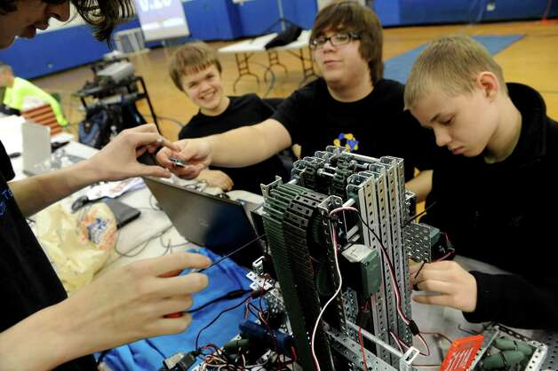 The Averill Park High School team of Alex Thomas, left, Erik Dunn, Matt Bedell and Michael Hansen, right, work on their robot during the Skyrise VEX Robotics Competition at Maple Avenue Middle School on Saturday Dec. 13, 2014 in Saratoga Springs , N.Y.  (Michael P. Farrell/Times Union) Photo: Michael P. Farrell / 00029837A