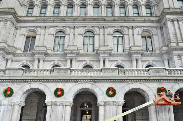 OGS workers Arnie Buell and Rick Nieto, right, hang holiday wreaths over the State Street entrance to the NYS Capitol Saturday Dec. 13, 2014, in Albany, NY.  (John Carl D'Annibale / Times Union) Photo: John Carl D'Annibale