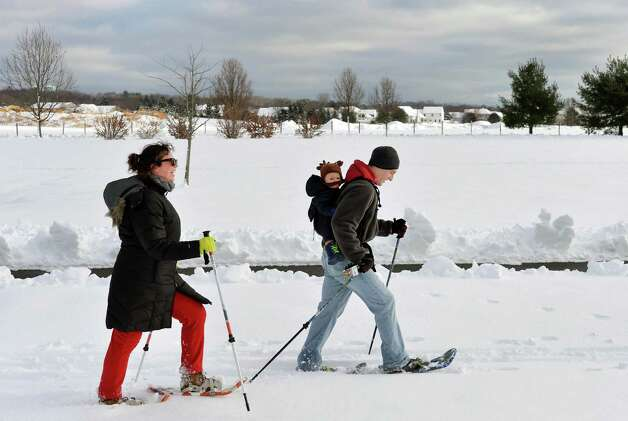 Gabrielle Walker, left, of Watervliet, her husband Andrew and 1-yr-old son Patrick snowshoe for the first time ever at The Crossings of Colonie Saturday Dec. 13, 2014, in Colonie, NY.  (John Carl D'Annibale / Times Union) Photo: John Carl D'Annibale