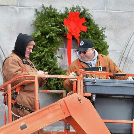 OGS workers Arnie Buell, left, and Rick Nieto hang holiday wreaths over the State Street entrance to the NYS Capitol Saturday Dec. 13, 2014, in Albany, NY.  (John Carl D'Annibale / Times Union) Photo: John Carl D'Annibale