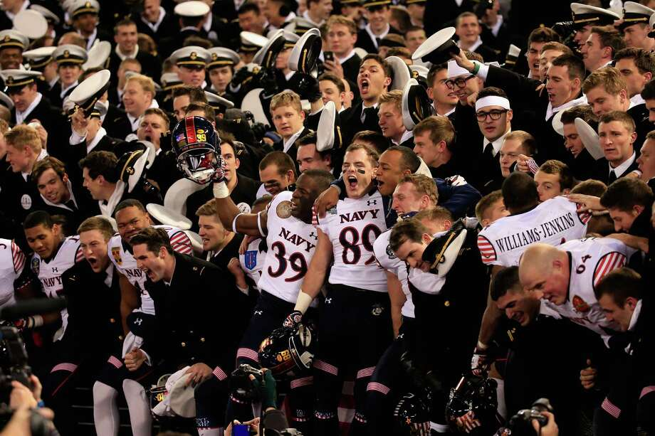 Navy teammates celebrate with fellow cadets in the stands after beating Army 17-10. Photo: Rob Carr / Getty Images / 2014 Getty Images