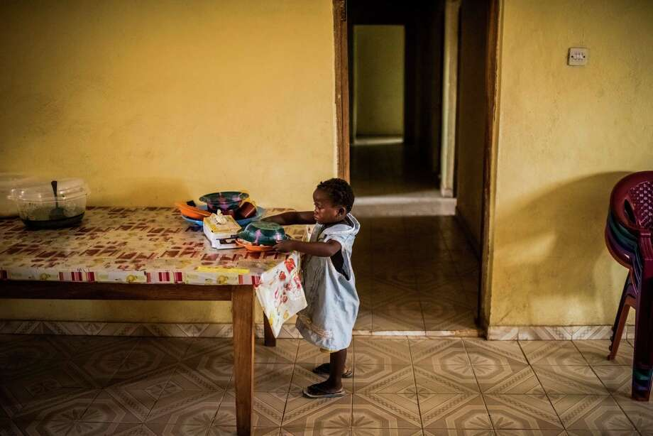 Sweetie Sweetie, believed to be 4, covers her lunch before hiding it in her room at the group home where she now lives in Port Loko, Sierra Leone. The child, whose family died of Ebola, worries about getting adopted. Photo: DANIEL BEREHULAK, STR / NYTNS