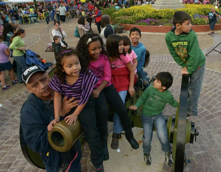 Michael Bueno holds his granddaughter, Natalie Mauricio, 6, as they and others play on a cannon at the