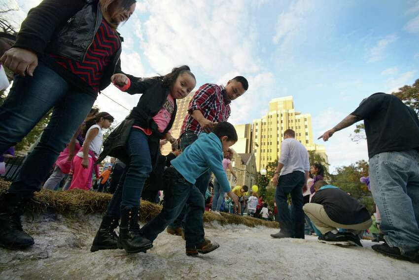 Children take tentative steps onto the ice and snow at the