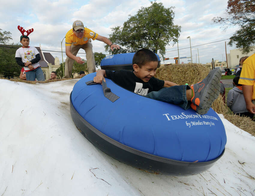 Omar Maldonado pushes children on inner tubes down a snow ramp at the