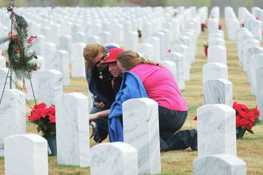 Almena Fritz, 71, at left and widow of Master Sgt. Robert Emil Fritz, consoles her grandson Dustyne Arik Fritz, 15, at Fort Sam Houston National Cemetery prior to the start of the Wreaths Across America ceremony on Dec. 13. At right is Dustyne's mother and Almena's daughter-in-law Della Fritz. Robert Fritz was a 20-year Air Force veteran and a San Antonio native.  He was a member of the first graduating class at Highland's High School in 1959. Photo: Luis Rios / San Antonio Express-News / San Antonio Express-News