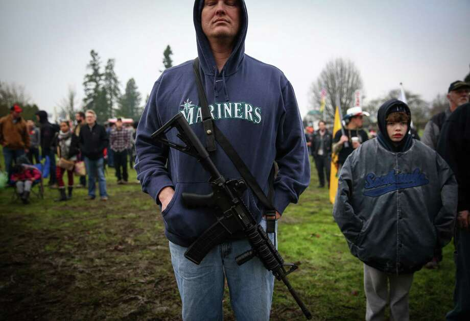 A participant holds a semi-automatic rifle as opponents of a Washington State law requiring mandatory background checks on all guns sales gather on the grounds of the State Capitol in Olympia. The law, known as Initiative 594, was passed by voters in November. Photographed on Saturday, December 13, 2014. Photo: JOSHUA TRUJILLO, SEATTLEPI.COM / SEATTLEPI.COM