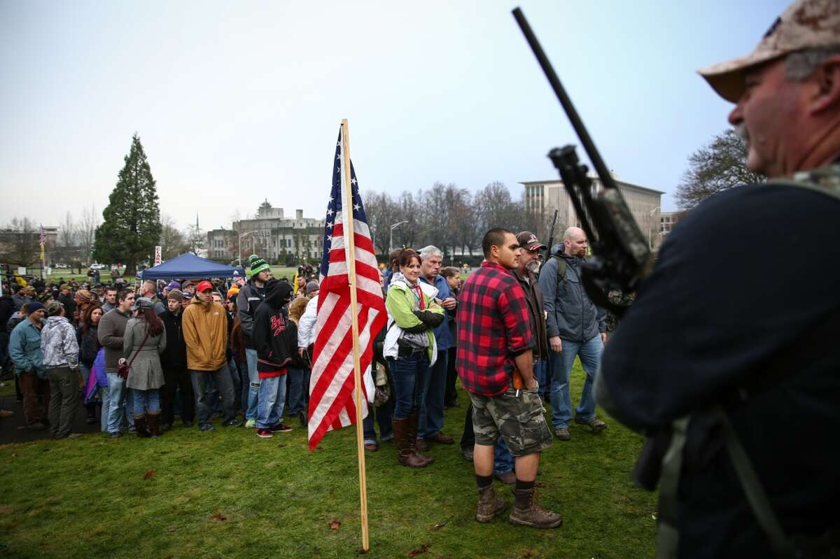 People line up to sign an intent to defy a Washington State law requiring mandatory background checks on all guns sales as people gather on the grounds of the State Capitol in Olympia. The law, known as Initiative 594, was passed by voters in November. Photographed on Saturday, December 13, 2014. (Joshua Trujillo, seattlepi.com)