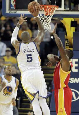 Marreese Speights (5) puts in a shot over Joey Dorsey (8) in the second half at Oracle Arena in Oakland, Calif., on Wednesday, December 10, 2014. The