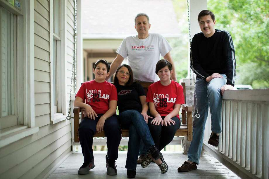 John DiFilippo, background, his wife Arianna, seated center, and their three children, Marco, left, Isabella and Brian, believe in the potential of Hogg Middle School. Marco, 11, and Isabella, 14, both attend the community school. Photo: Marie D. De Jesus, Staff / © 2014 Houston Chronicle